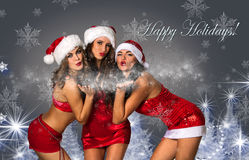 Three Sexy Santa's Helpers blowing snow Stock Photos