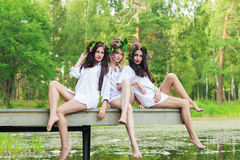 Three sexy woman sitting on a wooden bridge Stock Photo