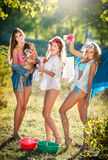 Three sexy women with provocative outfits putting clothes to dry in sun. Sensual young females laughing putting out the washing Stock Image