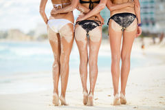 Three sexy women's butt in the sand on the beach. Royalty Free Stock Photos