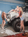 Three sexy women washing car Royalty Free Stock Photos