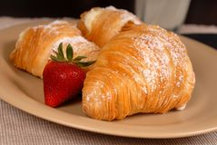 Three sfogliatelle's with strawberry. On tan plate Stock Images