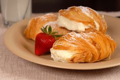 Three sfogliatelle's with strawberry on tan plate. Three sfogliatelle's filled with pastry cream with strawberry Royalty Free Stock Image