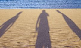 Three shadows on the beach stock image
