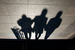 The three shadows. Shadows of three people coming down the stairs at the Galata Bridge, Istanbul, Turkey royalty free stock photos
