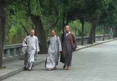 Three shaolin monks go somewhere. DENGFENG, CHINA - JUNE 20, 2013 Three shaolin monks go somewhere from Shaolin monastery near Dengfeng, China on 20th June, 2014 stock photo