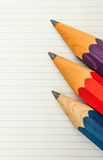 Three sharp thick pencils and lined paper Stock Photography