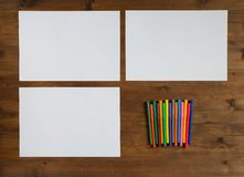Three sheet of paper and colored markers Stock Images