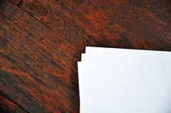 Three sheets of white paper lying on a  wooden  surface Stock Image