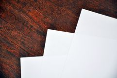 Three sheets of white paper lying on a  wooden  surface Stock Images