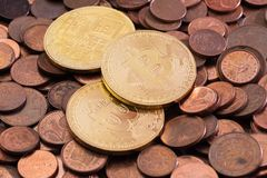 Three new shiny Bitcoins laying on a pile of used euro cent copper coins royalty free stock photos