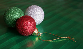 Three Shiny Christmas Baubles. Sitting on green wrapping paper Royalty Free Stock Photography
