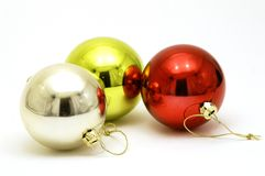 Three shiny Christmas decorations. Red gold and silver Christmas baubles Stock Images