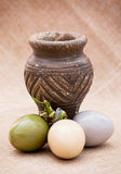 Three shiny easter eggs with ceramic vase Royalty Free Stock Images