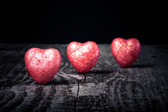 Three shiny red hearts on old wooden background. Toned Royalty Free Stock Image