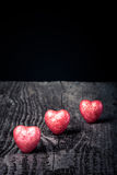 Three shiny red hearts on old wooden background. Toned Stock Photos