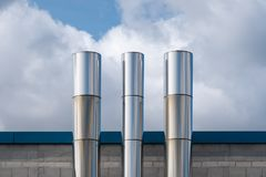 Three Shiny Stainless Steel Chimneys royalty free stock image