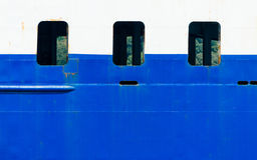 Three ship porthole windows on blue and white vessel Stock Photo