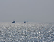Three ships, misty sky, sun reflection Stock Photo