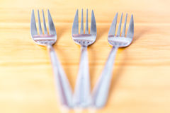 Three shniy metallic forks on a wooden table Royalty Free Stock Photo