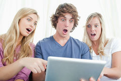 Three shocked friends looking at the screen of the tablet Stock Image