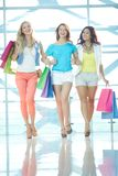Three shoppers in the mall Royalty Free Stock Image