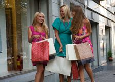 Three shopping friends. Three shopping girl friends near shop stock images