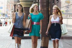 Three shopping girlfriends walking Stock Photos