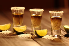 Three Short Glasses With Alcohol Next To A Slice Of Lime And Salt Are On An Old Rustic Table With Vintage Texture Royalty Free Stock Photo