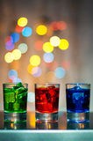 Three shot glasses with cocktail or liquor. Happy Royalty Free Stock Images