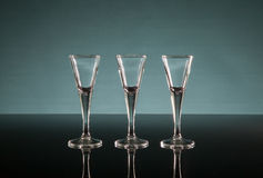 Three shot glasses. Shot glasses on a polished surface with a blueish background Stock Photo