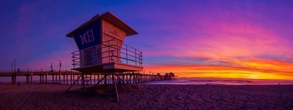 Huntington Beach at sunset. Three shot stich panorama of the Huntington Beach pier and a life guard tower with the HB logo Royalty Free Stock Images