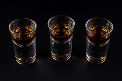 Three shots with cognac or jager on black Stock Image