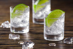 Three shots with gin and tonic. Three glasses with gin and tonic served with ice and lime on a wooden table stock photos