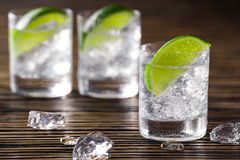 Three shots with gin and tonic. Three glasses with gin and tonic served with ice and lime on a wooden table royalty free stock image