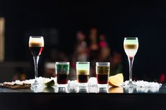 Three shots in glasses b-52 and two shots in glasses on the bar table. Royalty Free Stock Image