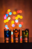 Three shots glasses full of assorted beverages and Royalty Free Stock Images