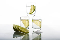 Three shots of vodka with lime Royalty Free Stock Photos