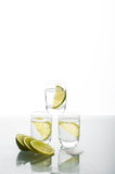 Three shots of vodka with lime Royalty Free Stock Photo
