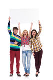 Three shouting young people with banner. Three young students holding white blank banner over head and shouting. Full length studio shot isolated on white Royalty Free Stock Image