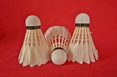 Three shuttlecocks on red frieze background Royalty Free Stock Image