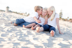 Three Sibling Children Kissing the Youngest Stock Photography