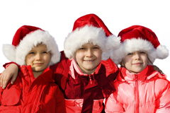 Three siblings dressed as Santas.  Stock Photography