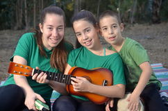 Three siblings playing musical instruments Royalty Free Stock Photography