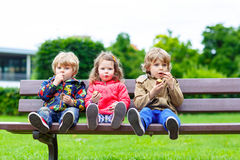 Three siblings sitting on bench and eating chocolate. Royalty Free Stock Image