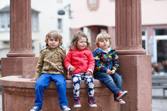 Three siblings sitting together on fountain in city Royalty Free Stock Photos