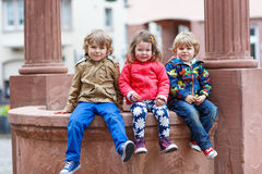 Three siblings sitting together on fountain in city Royalty Free Stock Photography