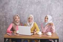Three siblings wearing hijab having project together. Portrait of three siblings wearing hijab having project together Royalty Free Stock Image