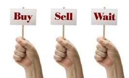 Three Signs In Fists Saying Buy, Sell and Wait. Three Signs In Male Fists Saying Buy, Sell and Wait Isolated on a White Background Royalty Free Stock Image