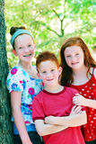 Three siblings outdoors. Three silblings, two girls and a boy posing outdoors Royalty Free Stock Images